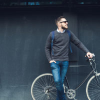 A young stylish hipster posing next to his bicycle.