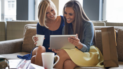 Two young women sitting on the couch drinking coffee and working on a digital tablet
